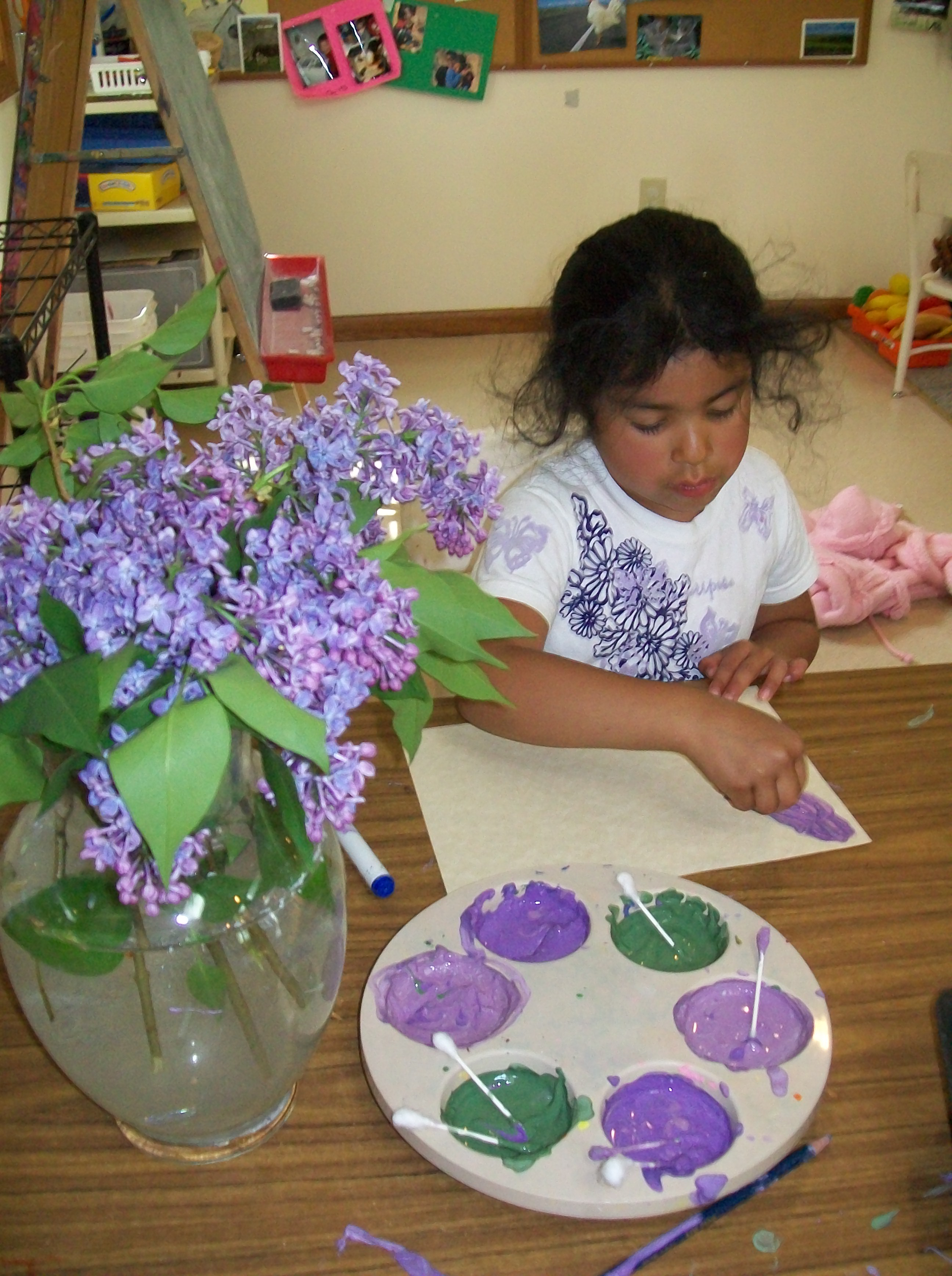 Child painting inspired by bouquet of lilacs.